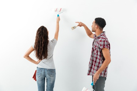 Back view of man and woman making repair isolated over whit background