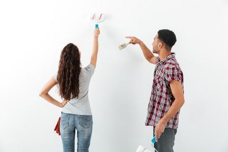 Hintere Ansicht des Mannes und der Frau, welche die Reparatur lokalisiert über Whithintergrund macht Standard-Bild - 82149246
