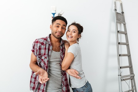 Beautiful amusing young couple holding brushes and having fun over white background Stock Photo