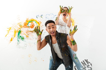 Happy young couple painting by hands and having fun over white background 免版税图像