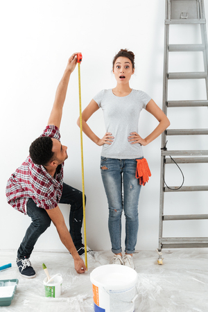 Man using measure tape to measure his shocked glad wowan standing near ladder isolated Stock Photo