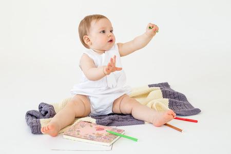 Beeld van de zitting van het babymeisje op vloer op plaid dichtbij tellers en kleuren geïsoleerd over witte achtergrond. Opzij kijken. Stockfoto