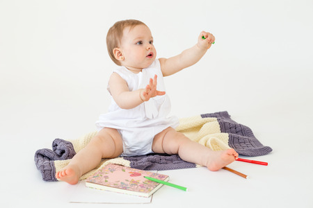 Image of baby girl sitting on floor on plaid near markers and colouring isolated over white background. Looking aside.