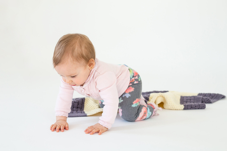 Picture of pretty baby girl sitting on floor with plaid isolated over white background. Looking aside. Stock Photo