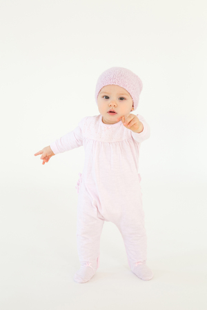 Picture of cute little baby wearing hat standing on floor isolated over white background. Looking at camera.