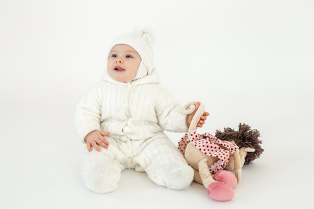 Image of cute little baby sitting on floor over white background. Looking aside and holding toy.