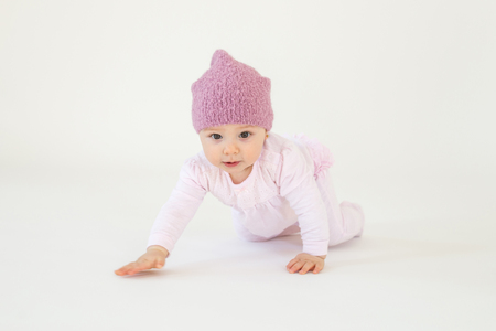 Picture of cute little baby girl wearing hat sitting on floor isolated over white background. Looking at camera. Stock fotó