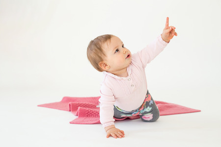 白い背景で隔離の床に座ってのかわいい女の子のイメージ。よそ見と指摘します。 写真素材