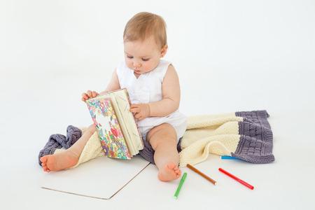 Beeld van de leuke zitting van het babymeisje op vloer op de tellers van de plaidholding en kleuring die over witte achtergrond wordt geïsoleerd. Opzij kijken. Stockfoto