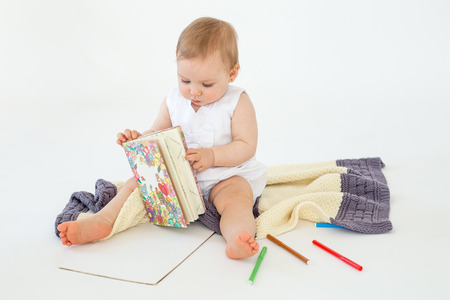 Image of cute baby girl sitting on floor on plaid holding markers and colouring isolated over white background. Looking aside.