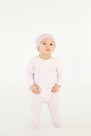 Picture of cute little baby wearing hat standing on floor isolated over white background. Looking aside.