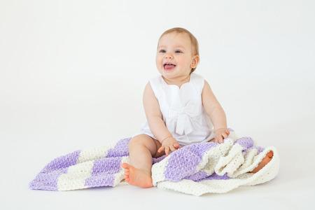 Beeld van de vrolijke die kleine zitting van het babymeisje op vloer met plaid over witte achtergrond wordt geïsoleerd. Opzij kijken. Stockfoto
