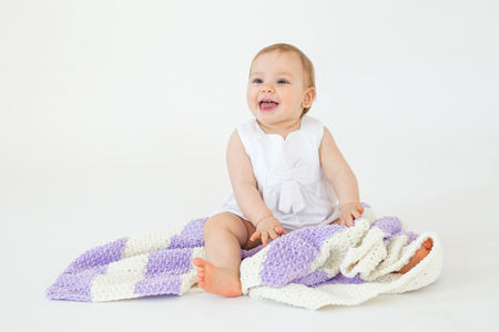 Image of cheerful little baby girl sitting on floor with plaid isolated over white background. Looking aside. Stock fotó
