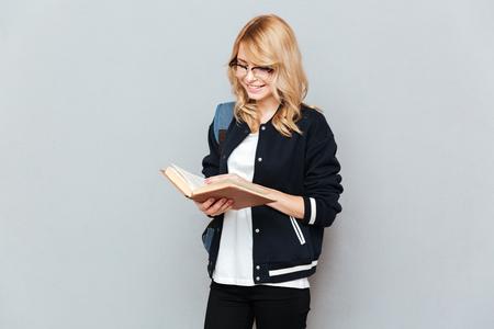 Boek van de de studentenlezing van de blonde het jonge vrouw dat over grijze achtergrond wordt geïsoleerd