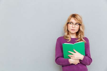 Upset young woman with opened book looking away and thinking isolated