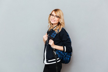 Image of cheerful young lady wearing glasses student with backpack posing over grey wall. Looking at camera.