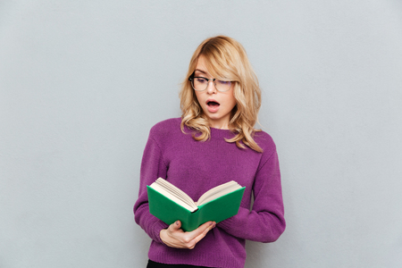 開いた口が付いている本を読んで驚いたの若い女性