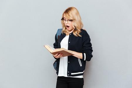 Verrast vrouwelijke student leesboek geïsoleerd Stockfoto