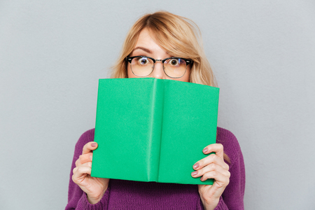 Woman in glasses hiding face with green book