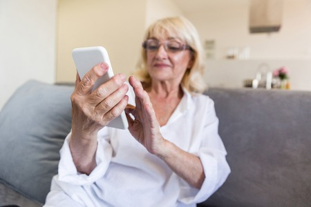 Beautiful senior woman in eyeglasses using a smartphone and smiling while sitting on couch at home Banco de Imagens