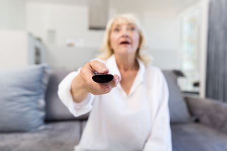 Senior woman changing channel with remote control while sitting on a sofa at home Stock Photo