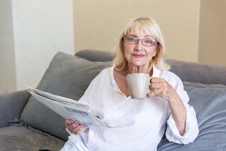 Senior woman in eyeglasses holding a newspaper while having a cup of coffee in the morning on a couch a home Stock Photo - 82324922