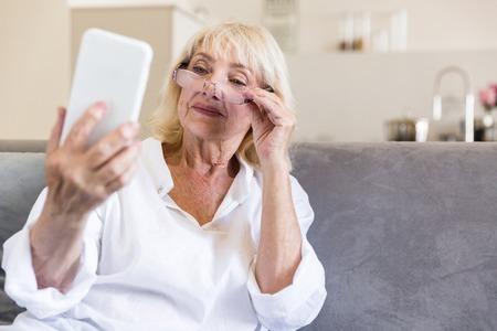 眼鏡メッセージをスマート フォンで読み取ると、自宅でソファに座って笑顔で美しいシニア女性