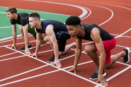 Image of multiethnic athlete group ready to run on running track outdoors. Looking aside.