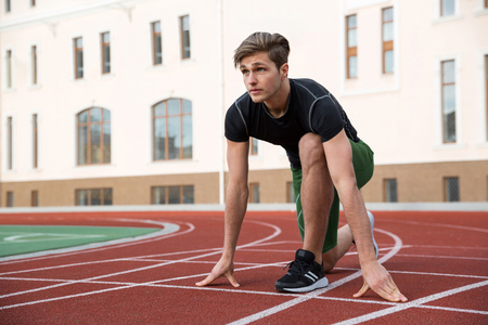 Picture of handsome young male athlete ready to run on running track outdoors. Looking aside.