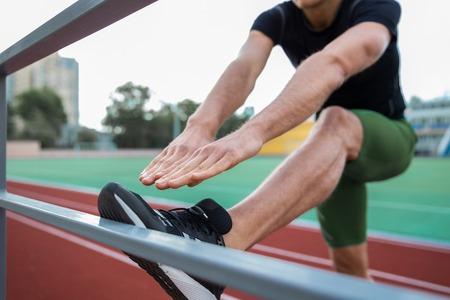 若い男選手のトリミングされた画像は、屋外のストレッチ体操を作る。