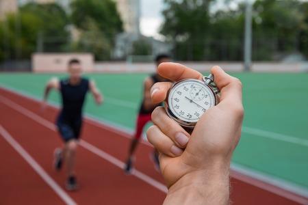 若い選手は男性の画像は屋外ランニング トラックで実行します。歴史的な停止時計時間の測定。 写真素材