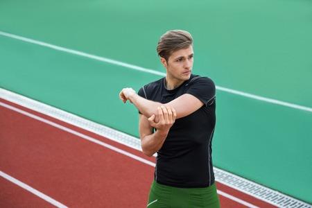 集中の若い選手は男性のイメージは、屋外のストレッチ体操を作る。よそ見。