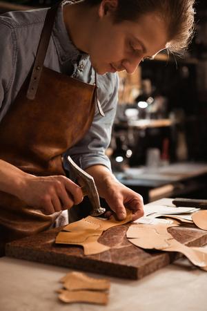 Schließen Sie oben von einem Schustermann, der mit Leder unter Verwendung der Herstellungswerkzeuge arbeitet