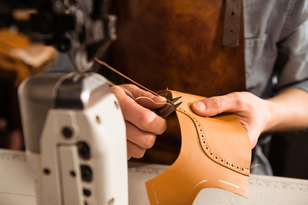 Man artisan sewing leather shoes indoors at a workshop Stock Photo