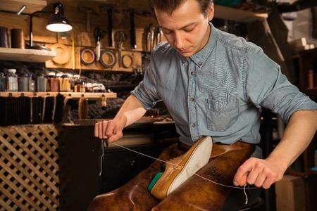 靴を作るワーク ショップで若い集中靴屋の写真。よそ見。