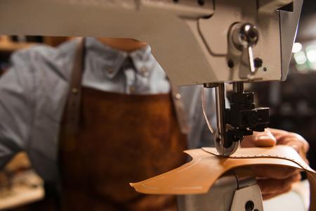 Close up of a cobbler using sewing machine at a workshop Foto de archivo