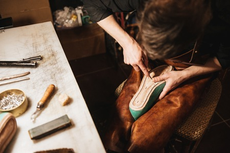 heavy: Cropped photo of young man shoemaker at footwear workshop.