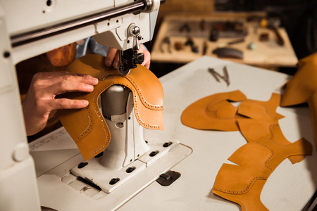 Close up of a male craftsman stitching leather parts on a sewing machine at a workshop