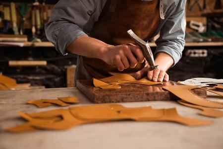 Schließen Sie oben von einem Schustermann, der mit Leder unter Verwendung der Herstellungswerkzeuge arbeitet Standard-Bild