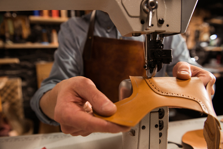 Man cobbler stitching leather patrs on a sewing machine Standard-Bild