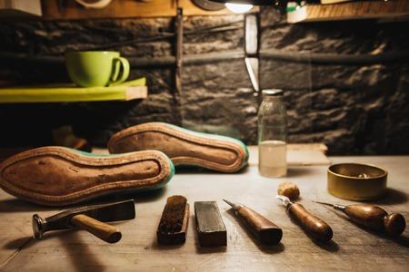 신발 및 신발 워크숍 테이블에 악기의 이미지.