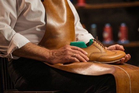 Cropped picture of mature shoemaker in workshop making shoes.