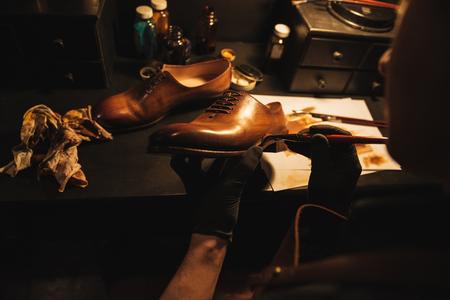 若い男が集中して靴屋靴のワーク ショップでの画像をトリミングしました。 写真素材