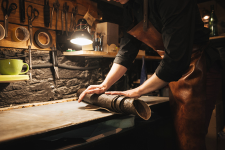 Cropped image of concentrated man shoemaker at footwear workshop.