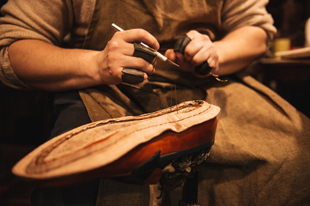 Cropped photo of young man shoemaker at footwear workshop.