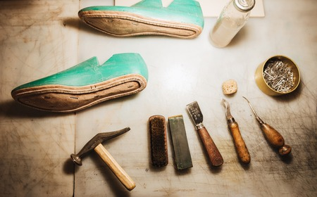 Image of shoes and instruments on table at footwear workshop.
