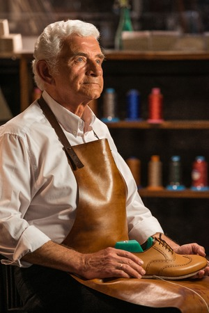Image of mature handsome shoemaker in workshop holding shoes. Looking aside.
