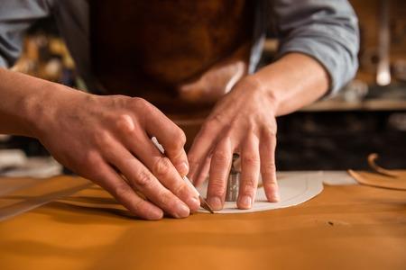 Close-up van een schoenmaker snijden leer in een werkplaats