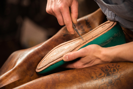 Cropped image of bootmaker sitting in workshop making shoes