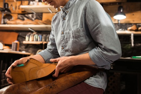 Cropped photo of shoemaker sitting in workshop making shoes